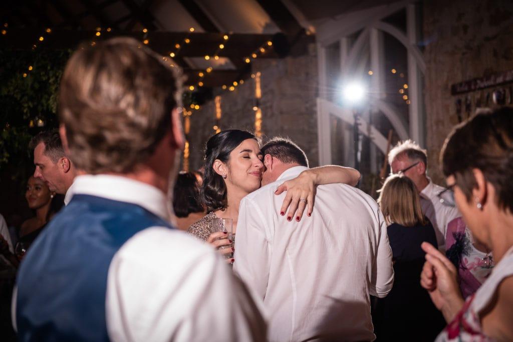 wedding guests hugging on dance floor
